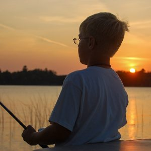 Young male child fishing with sunset on the lake